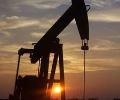 Image contains the silhouette of a horsehead oil pump against the evening sky