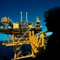 Silhouette of a rig worker against offshore rig