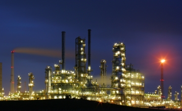 Bright lights of a refinery seen against a dark blue evening sky